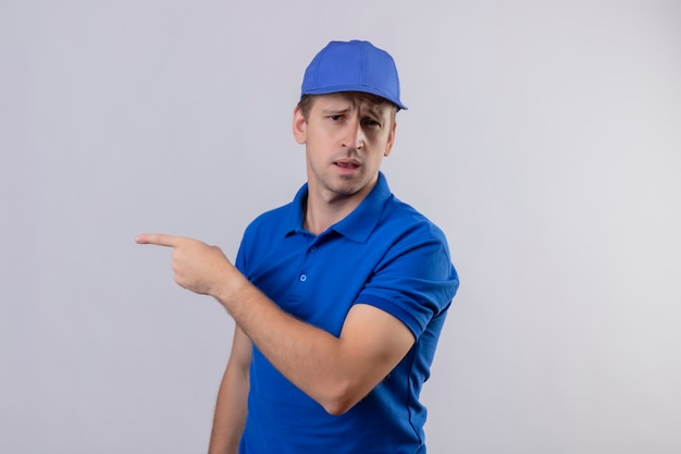 Jonge knappe bezorger in blauw uniform en pet wijzend met wijsvinger naar de zijkant op zoek verward staande over witte muur
