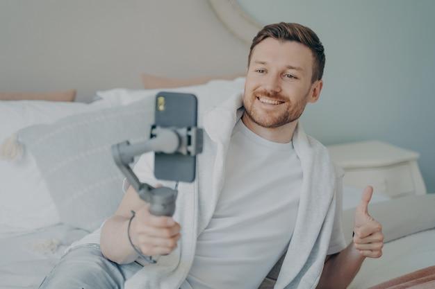 Jonge knappe blanke bebaarde man doet online bellen met webcam met smartphone terwijl hij thuis op bed ligt, blij met een grote glimlach doet super cool teken duim omhoog met vingers