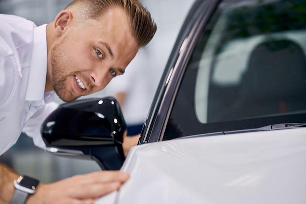 Jonge knappe blanke man controleert het oppervlak van de auto