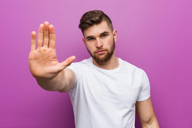 Jonge knappe blanke man die met uitgestrekte hand stopbord tonen, waardoor u.