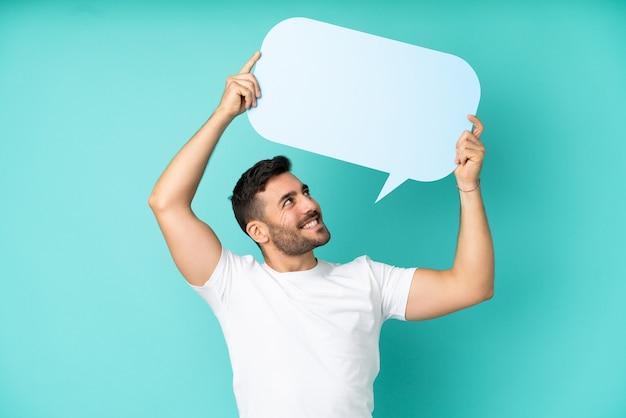 Jonge knappe blanke man geïsoleerd op blauwe achtergrond met een lege tekstballon