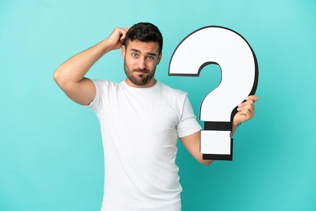 Jonge knappe blanke man geïsoleerd op blauwe achtergrond met een vraagtekenpictogram en twijfels