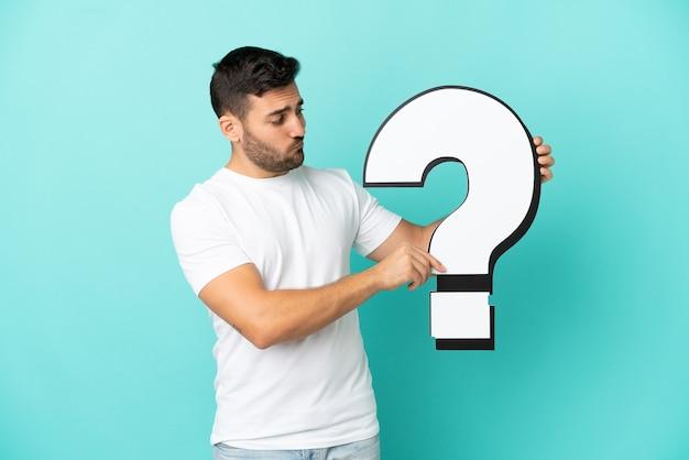Jonge knappe blanke man geïsoleerd op blauwe achtergrond met een vraagtekenpictogram