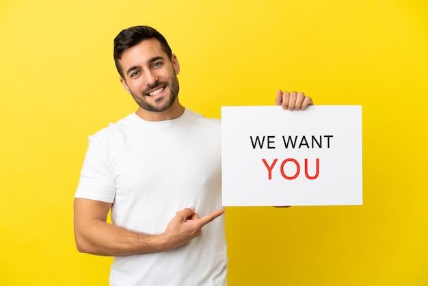 Jonge knappe blanke man geïsoleerd op een gele achtergrond die we want you-bord vasthoudt en erop wijst