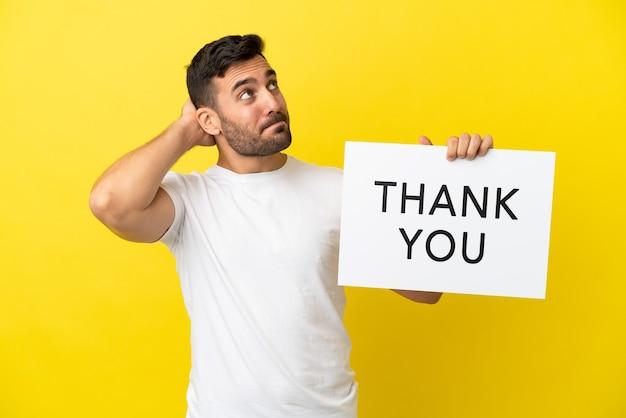Jonge knappe blanke man geïsoleerd op gele achtergrond met een bordje met de tekst dank u en denken