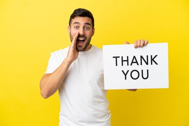 Jonge knappe blanke man geïsoleerd op gele achtergrond met een bordje met de tekst dank u en schreeuwen