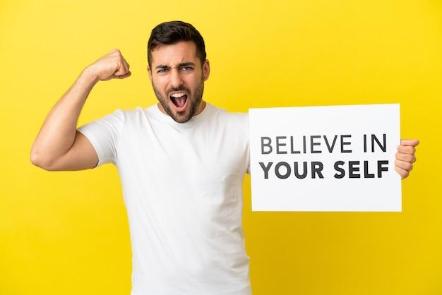 Jonge knappe blanke man geïsoleerd op gele achtergrond met een bordje met de tekst geloof in jezelf en een sterk gebaar doen
