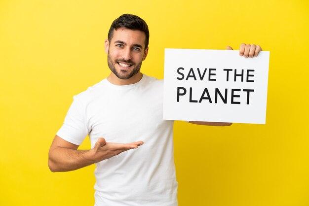 Jonge knappe blanke man geïsoleerd op gele achtergrond met een bordje met de tekst save the planet en erop wijzend