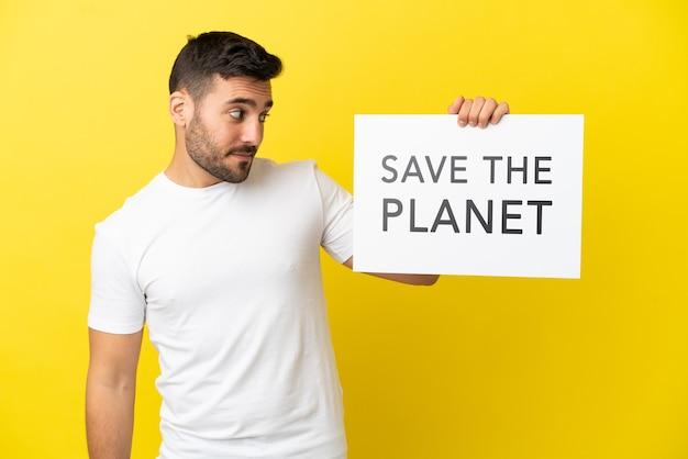Jonge knappe blanke man geïsoleerd op gele achtergrond met een bordje met de tekst save the planet
