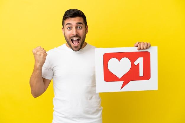 Jonge knappe blanke man geïsoleerd op gele achtergrond met een bordje met like-pictogram en een overwinning vieren