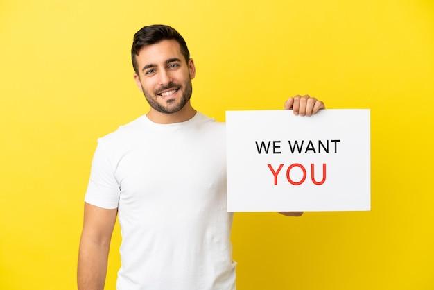 Jonge knappe blanke man geïsoleerd op gele achtergrond met we want you-bord met gelukkige uitdrukking
