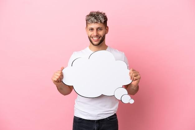 Jonge knappe blanke man geïsoleerd op roze achtergrond met een denkende tekstballon