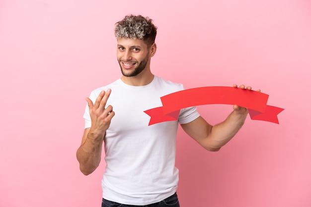 Jonge knappe blanke man geïsoleerd op roze achtergrond met een leeg bordje en komend gebaar doen