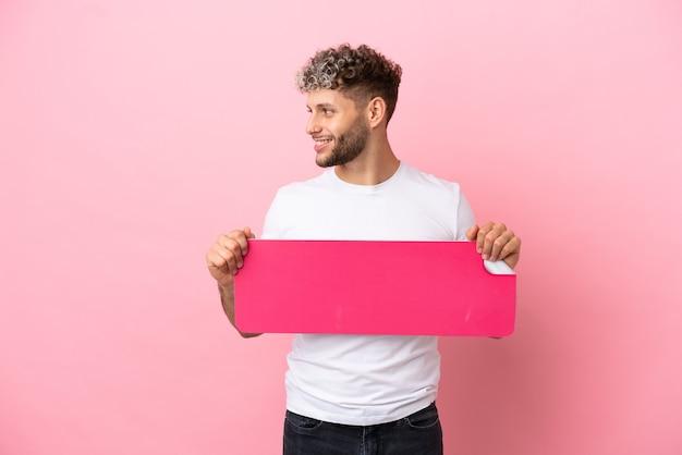 Jonge knappe blanke man geïsoleerd op roze achtergrond met een leeg bordje en opzij kijken