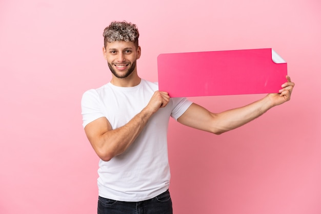Jonge knappe blanke man geïsoleerd op roze achtergrond met een leeg bordje