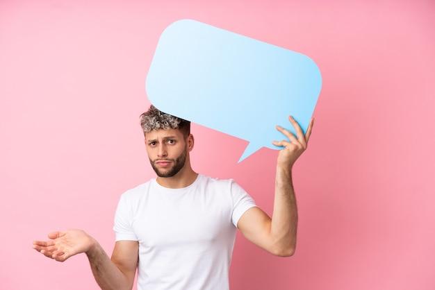 Jonge knappe blanke man geïsoleerd op roze achtergrond met een lege tekstballon en twijfels