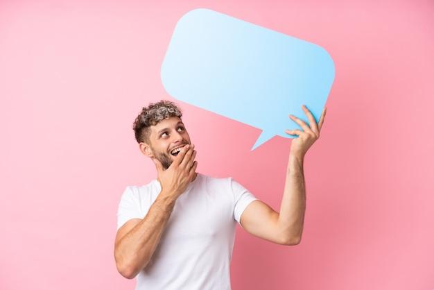 Jonge knappe blanke man geïsoleerd op roze achtergrond met een lege tekstballon met verbaasde uitdrukking