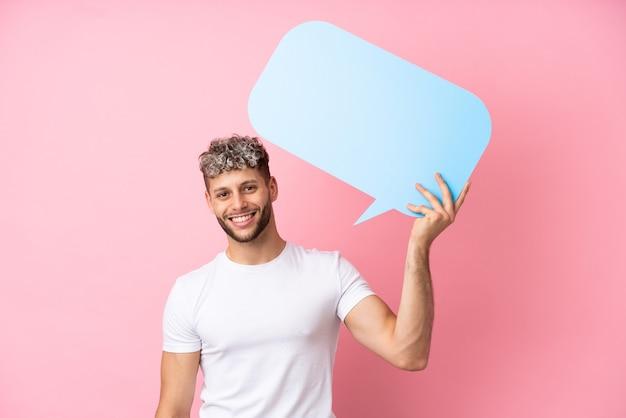 Jonge knappe blanke man geïsoleerd op roze achtergrond met een lege tekstballon