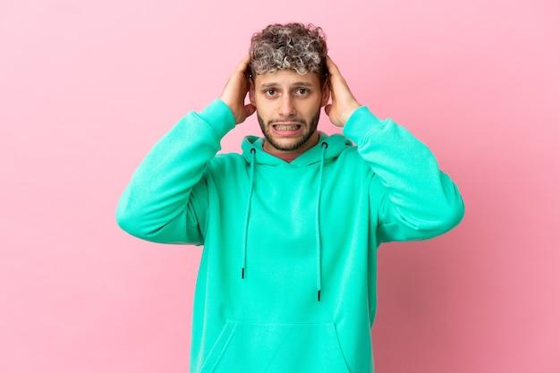 Jonge knappe blanke man geïsoleerd op roze achtergrond nerveus gebaar doen