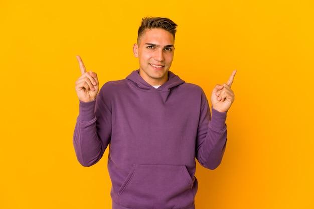 Jonge knappe blanke man geïsoleerd wijzend naar verschillende kopie ruimtes, het kiezen van een van hen, tonen met vinger.