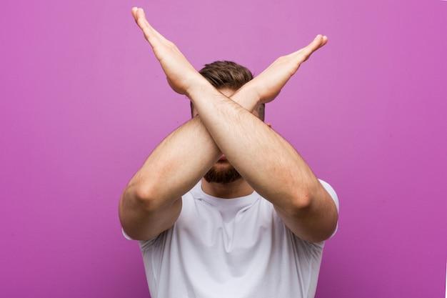 Jonge knappe blanke man houdt twee armen gekruist, ontkenning.