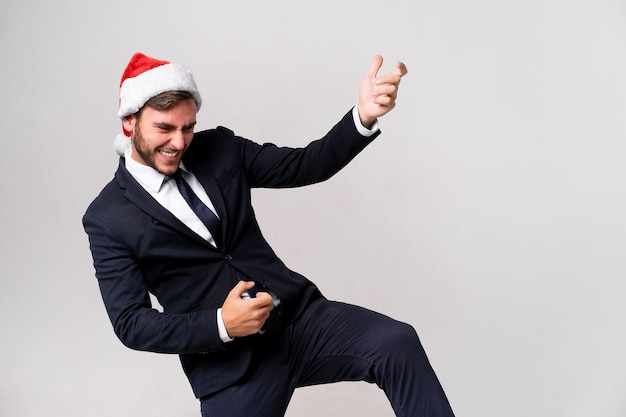 Jonge knappe blanke man in pak en kerstmuts