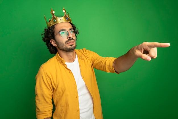 Jonge knappe blanke man met bril en kroon kijken en wijzend naar kant geïsoleerd op groene achtergrond
