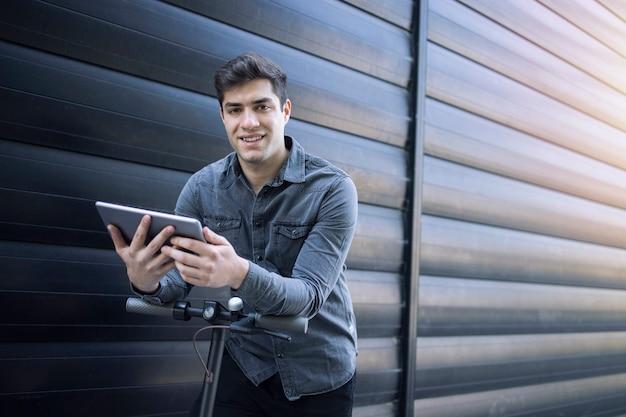 Jonge knappe blanke man op zijn elektrische scooter met tablet en op zoek naar de camera.