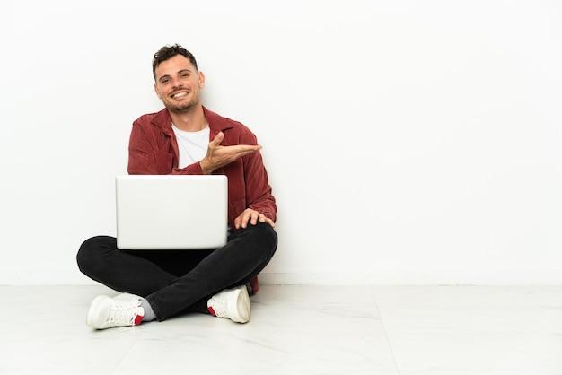 Jonge knappe blanke man sit-in op de vloer met laptop die een idee presenteert terwijl hij glimlachend naar kijkt