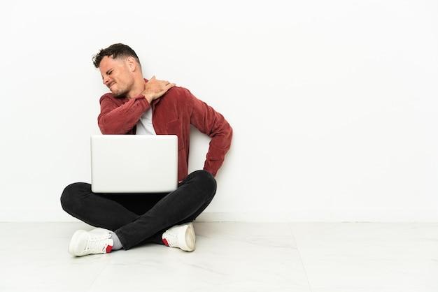 Jonge knappe blanke man sit-in op de vloer met laptop die lijdt aan pijn in de schouder omdat hij zich heeft ingespannen