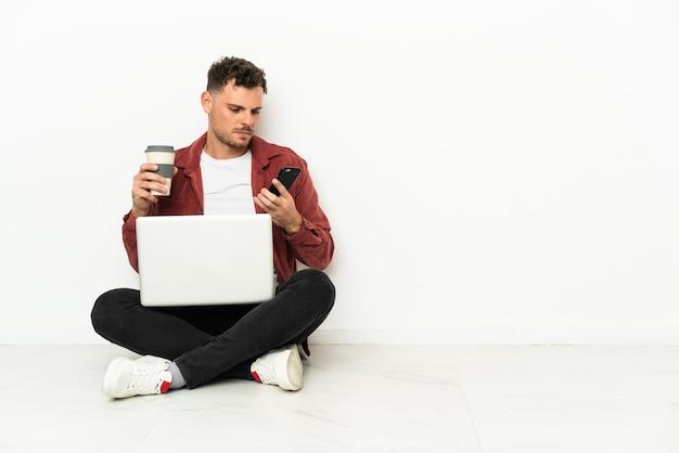 Jonge knappe blanke man sit-in op de vloer met laptop met koffie om mee te nemen en een mobiel