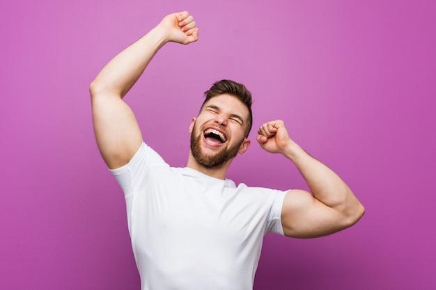 Jonge knappe blanke man viert een speciale dag, springt en verhogen armen met energie.