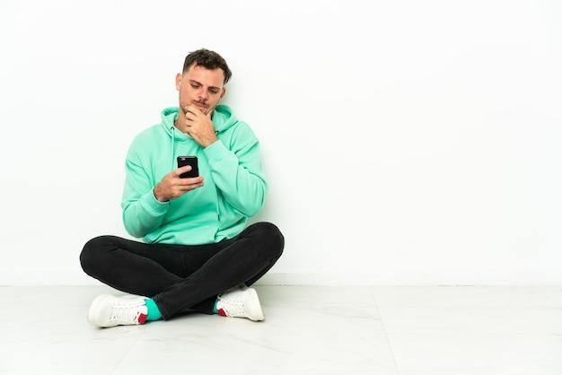 Jonge knappe blanke man zittend op de vloer denken en verzenden van een bericht