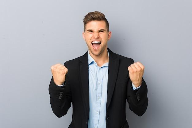 Jonge knappe blanke man zorgeloos en opgewonden juichen. overwinning concept.