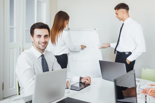 Jonge knappe blanke zakenman met een laptop op kantoor tijdens een presentatie.