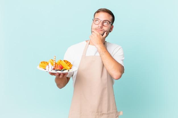 Jonge knappe blonde man denkt, voelt zich twijfelachtig en verward. wafels koken concept