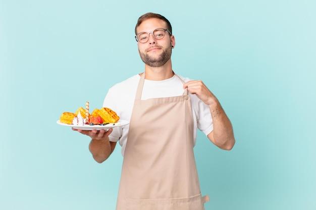 Jonge knappe blonde man die er arrogant, succesvol, positief en trots uitziet. wafels koken concept