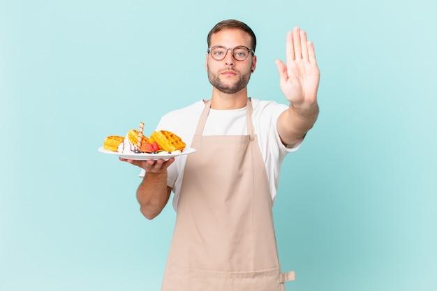 Jonge knappe blonde man die er serieus uitziet en open palm toont die een stopgebaar maakt. wafels koken concept
