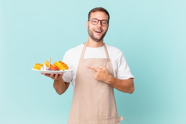 Jonge knappe blonde man die opgewonden en verrast kijkt en naar de zijkant wijst. wafels koken concept Premium Foto
