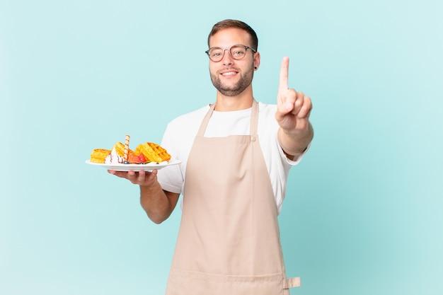 Jonge knappe blonde man die trots en zelfverzekerd glimlacht en nummer één maakt. wafels koken concept