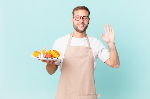 Jonge knappe blonde man die vrolijk lacht, met de hand zwaait, je verwelkomt en begroet. wafels koken concept