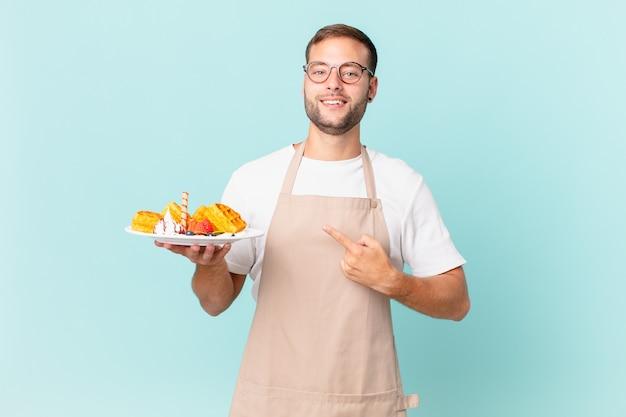Jonge knappe blonde man die vrolijk lacht, zich gelukkig voelt en naar de zijkant wijst. wafels koken concept