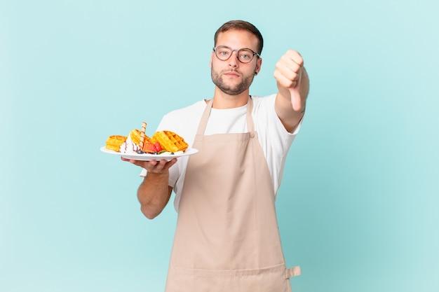 Jonge knappe blonde man die zich boos voelt en duimen naar beneden laat zien. wafels koken concept