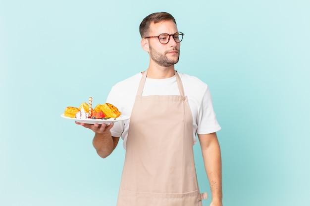 Jonge knappe blonde man die zich verdrietig, overstuur of boos voelt en opzij kijkt. wafels koken concept