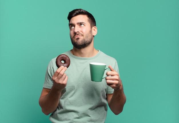 Jonge knappe blonde man met een chocolade donut en een koffiekopje. ontbijt concept Premium Foto