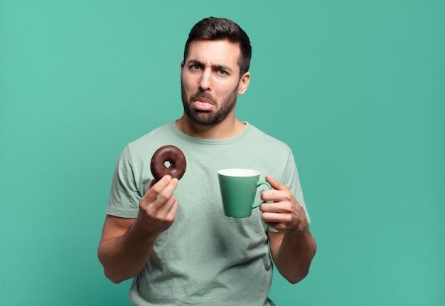 Jonge knappe blonde man met een chocolade donut en een koffiekopje. ontbijt concept
