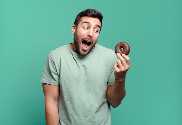 Jonge knappe blonde man met een chocolade donut. ontbijt concept