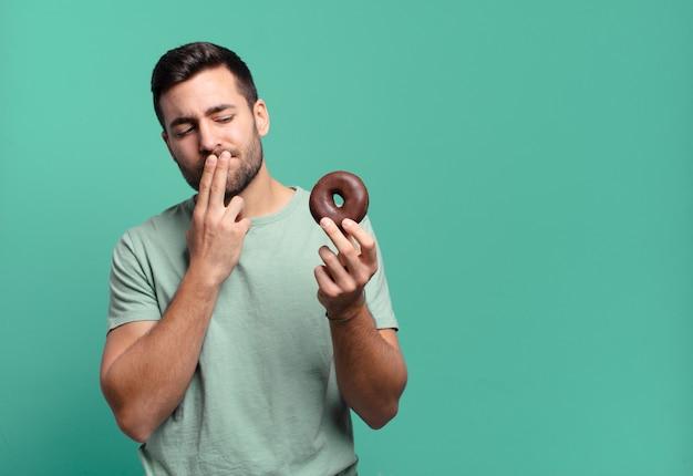 Jonge knappe blonde man met een chocolade donut.