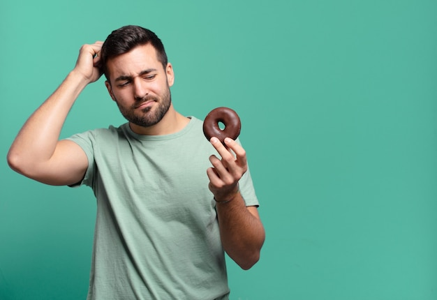 Jonge knappe blonde man met een chocoladedoughnut. ontbijt concept