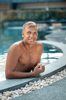 Jonge knappe blonde man poseren in het zwembad. zomervakantie. vakantie en reizen concept
